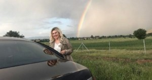 Shyhrete Behluli ndalon veturën në mes të rrugës për të bërë fotografi me peisazhin e ylberit